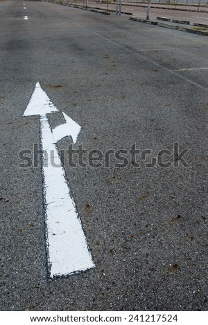 the arrow symbol on a black asphalt road surface - stock photo