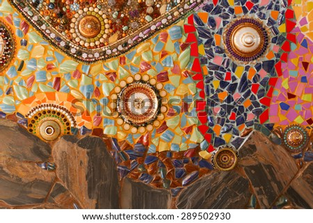 the art design of the colorful broken tile, dish, lid, bead and stone decorating on temple wall for abstract background