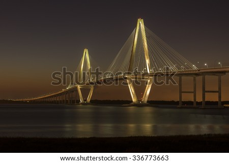 The Arthur Ravenel Jr. bridge illuminated against a darkening Spring sky.  The bridge carries eight lanes of traffic across the Cooper River, connecting Charleston and Mount Pleasant, SC, USA.