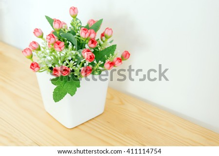 the artificial red flower in the pot at the wooden table with the white wall background.The hand made flower in the white pot at   wooden table.The beautiful red artificial flower in the white pot . - stock photo