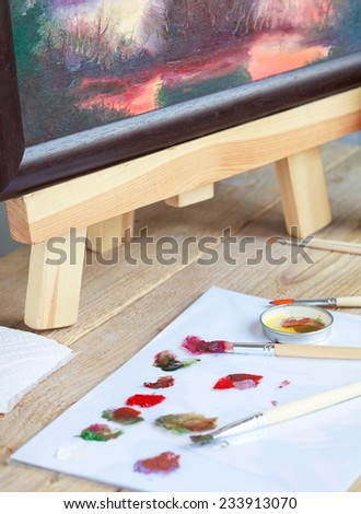 The artist paints a picture of the landscape using oil paints mounted on an easel. Selective focus on red brush - stock photo