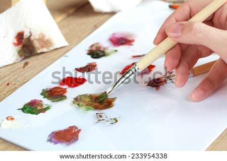 The artist paints a picture of the landscape using oily paints mounted on an easel. Selective focus on brush - stock photo