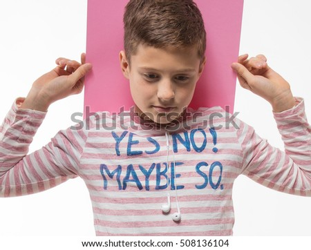 The artistic teenager boy brunette in a pink jumper with a pink sheet of paper for notes on a white background