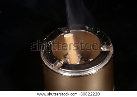 The ashtray with a cigarette, is photographed on a black background