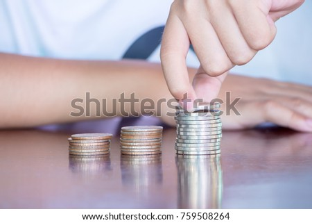 The Asian boy with glasses are stacking with coins to save the money for the future concept.