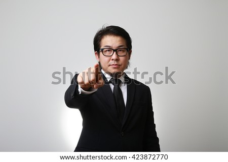 The Asian businessman pointing. - stock photo