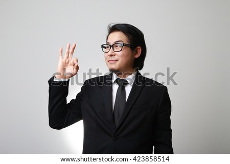 The Asian businessman showing okay sign. - stock photo