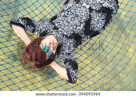 The Asian girl lying on the net above the sea.