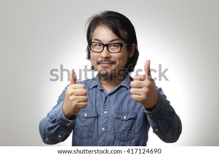 The asian man in blue denim shirt is showing thumb up. - stock photo