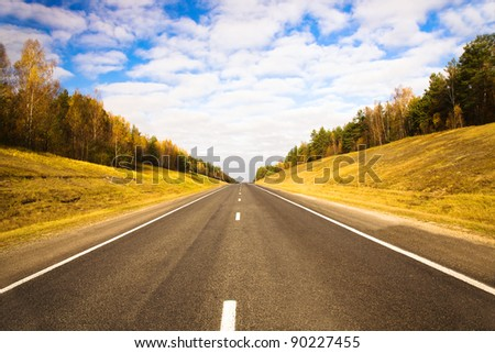 The asphalted small highway in an autumn season - stock photo