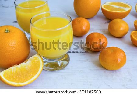 The assortment of juicy oranges, tangerines, sliced fruit and fresh orange juice - stock photo