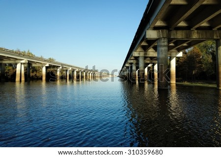 The Atchafalaya Basin Bridge and the Interstate 10 (I-10) highway seen from below on the water level of the Atchafalaya bayou on sunny late November evening in 2012 near Henderson, Louisiana. - stock photo