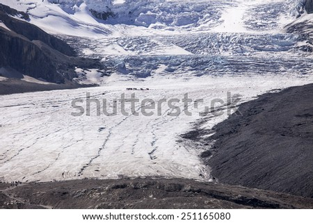 The Athabasca Glacier is formed from ice fall from the Columbia Ice Field. To show the huge scale, one group of trucks is in mid-glacier and a second group of people is at the tongue of the glacier. - stock photo