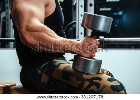 The athlete doing exercises for hands with dumbbells in a gym sitting on the bench - stock photo
