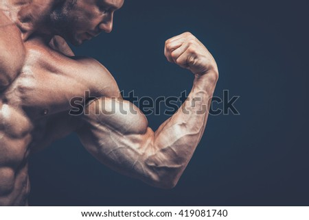The athlete shows his beautiful body on black background. - stock photo