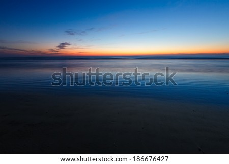 The Atlantic Ocean just before sunrise is photographed with longer exposure making the waves appear soft and dreamy.