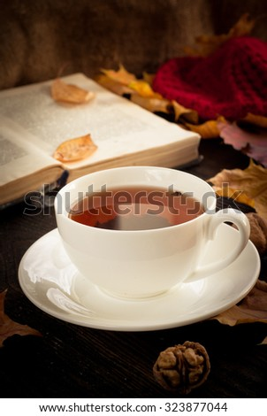 The atmosphere of autumn. A cup of hot tea, book and yellow leaves. Image toned in dark colors.