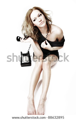 The attractive and sexual woman with phone on a white background - stock photo