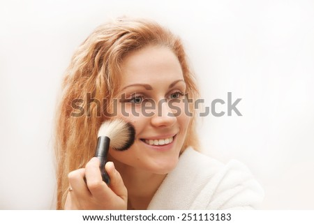 the attractive woman doing make-up on face.