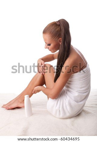 The attractive young woman in towel with cosmetic cream on a white background - stock photo