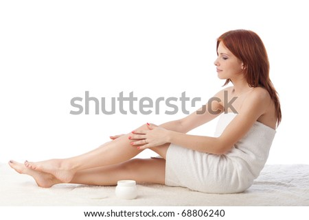 The attractive young woman in towel with cosmetic cream on a white background
