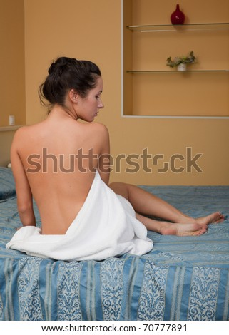 The attractive young woman in towel with cosmetic cream sits on bed at home. Concept of body care. - stock photo