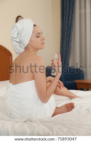 The attractive young woman in towel with cosmetic lotion sits on bed at home. Concept of body care.