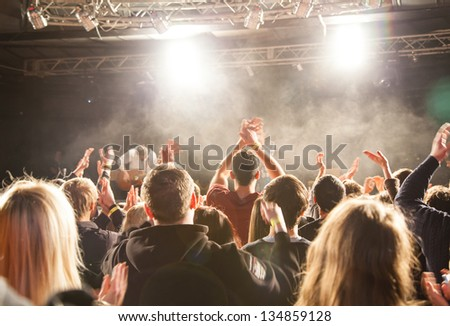 The audience applauded by the stage artist. They shines the spotlight. - stock photo