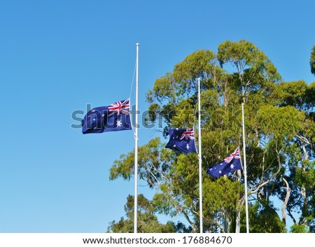 The Australian flags half mast in front of the war memorial building in Canberra in Australia - stock photo