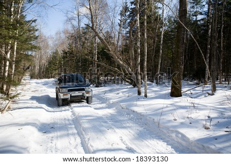 The automobile goes on snow-covered road in mountains.Winter. - stock photo