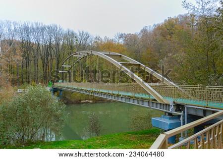 The autumn. The bridge over the river. - stock photo