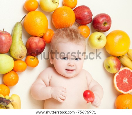The babe in an environment of the fresh fruit - stock photo