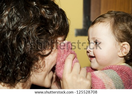 The baby and mother play cover his eyes./Baby and her mother are playing. - stock photo