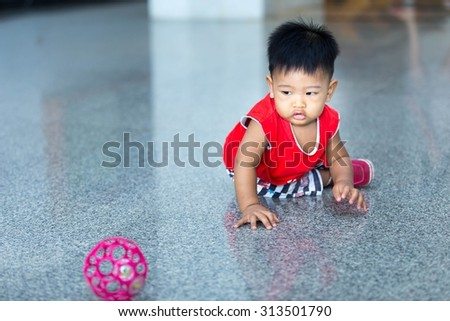 The baby Asian male wearing a red shirt. Crawling, playing on a cement floor inside the house. - stock photo