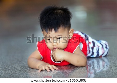 The baby Asian male wearing a red shirt. Crawling, playing on a cement floor inside the house.