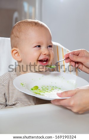 The baby boy eating with spoon at home