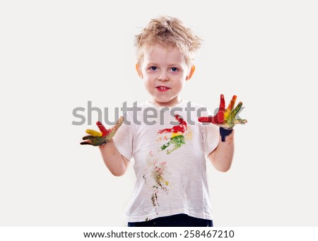 The baby boy with gouache soiled hands and shirt isolated on the white background