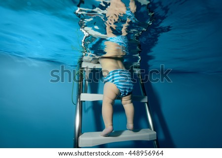 The baby down the stairs into the pool. The view from under the water. Horizontal orientation - stock photo