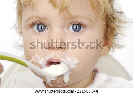 The baby girl eating with spoon with white background - stock photo