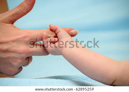 The baby has grasped a finger of mum - stock photo