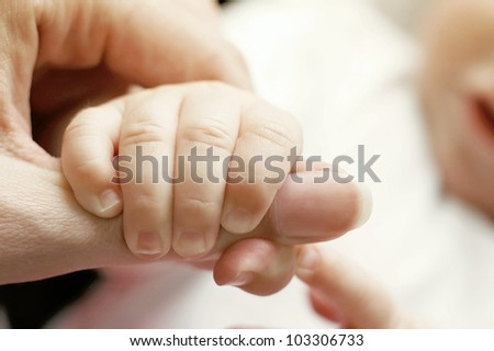 The baby holding parents finger