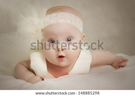 the baby in a dress lies on a pillow - stock photo