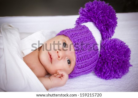 the baby in a violet knitted hat lies on a white cover - stock photo