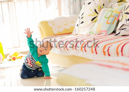 The baby is crawling on the floor - stock photo