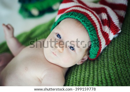 The baby is lying on a green knitted blanket in red and green and white striped cap. - stock photo