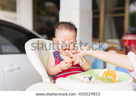 the baby learns to eat by himself. he can use his hand well. so he is very happy (focus at his face)