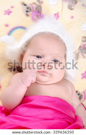The baby lies on a bed. Fleece blanket. Newborn one month. The girl with blue eyes. White hat and a pink blanket