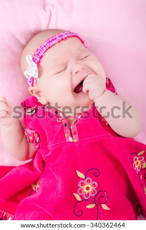 The baby lies on a bed. pink dress for girl. Newborn one month. The girl with blue eyes. Pink background. crying