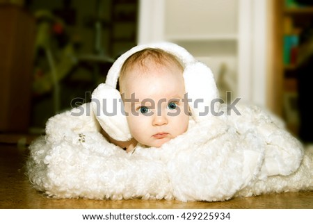 The baby lies on a white blanket with headphones.