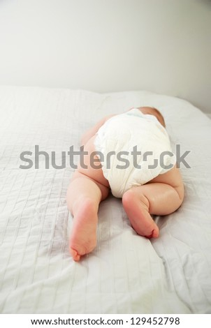 The Baby Lies on the Bed on his Stomach and Crawling